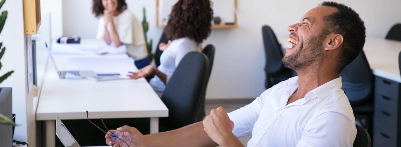 Personas riendo en el espacio laboral al practicar yoga de la risa