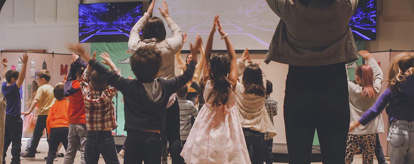 Niños y profesora bailando y saltano en grupo