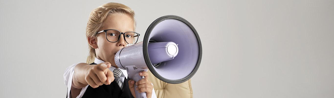 Mujer con un megafono señalando la pantalla