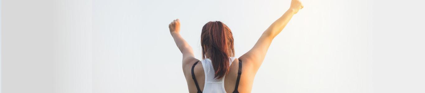 Imagen de una mujer de espalda alzando los brazos
