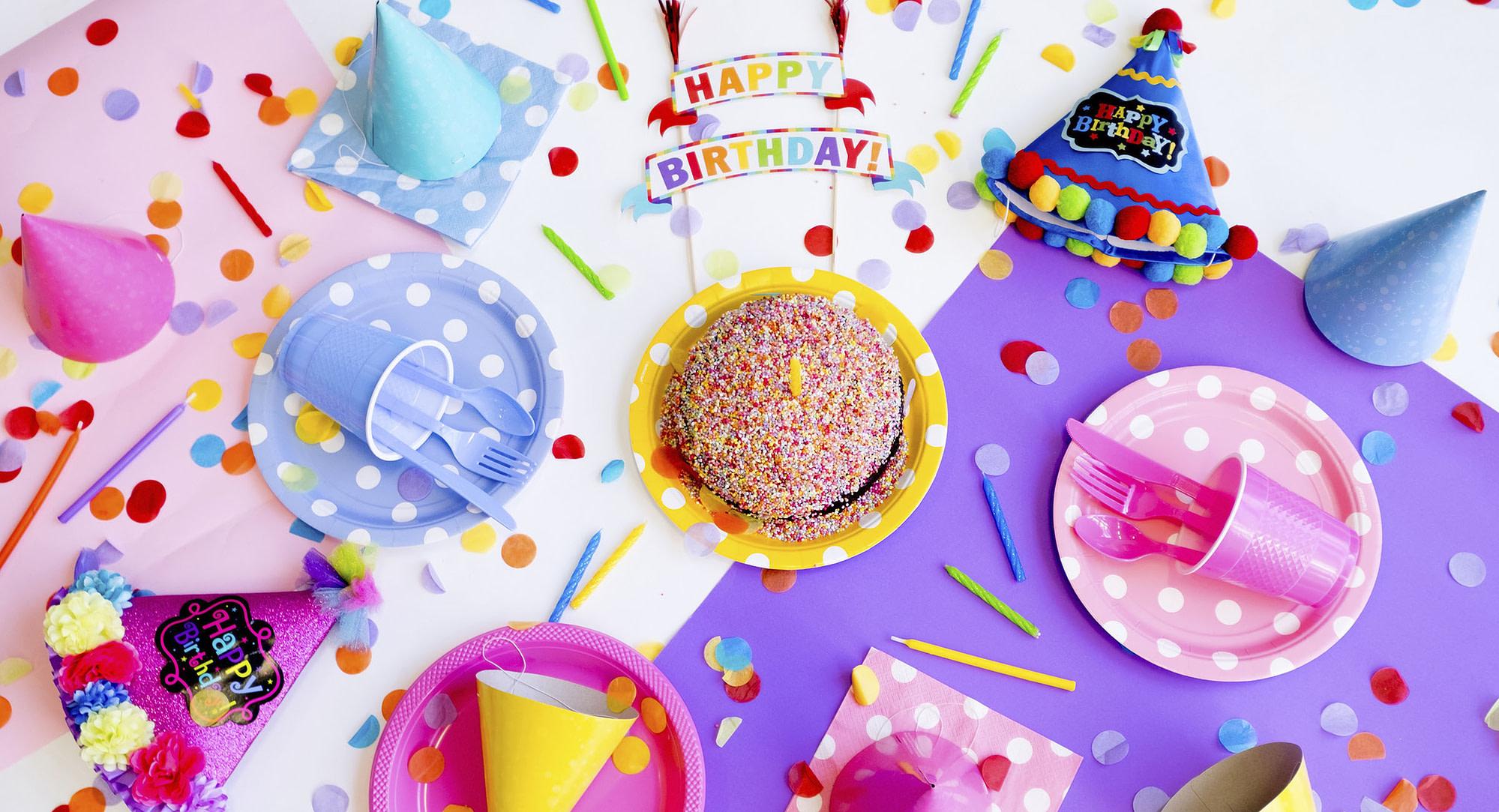 Mesa llena de papelillo, torta y gorros de cumpleaños en honor al aniversario número 20 de Siempre Baile