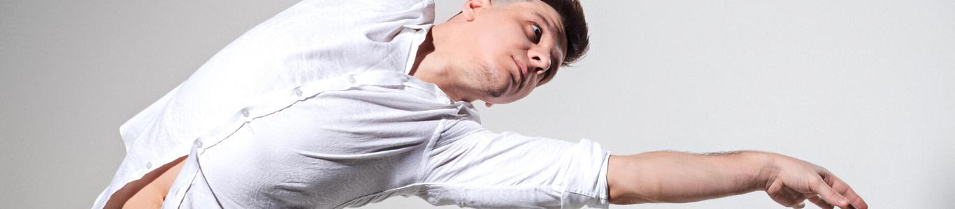 Imagen de un hombre bailando con camisa blanca.