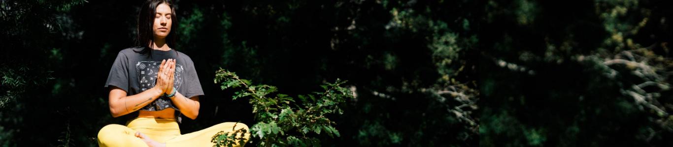 Imagen de una mujer meditando en un bosque