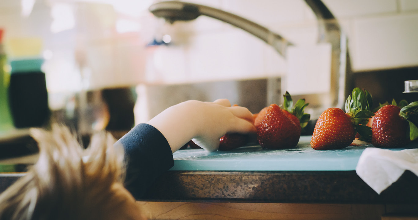 Niño tomando una fresa de un mesón para merendar